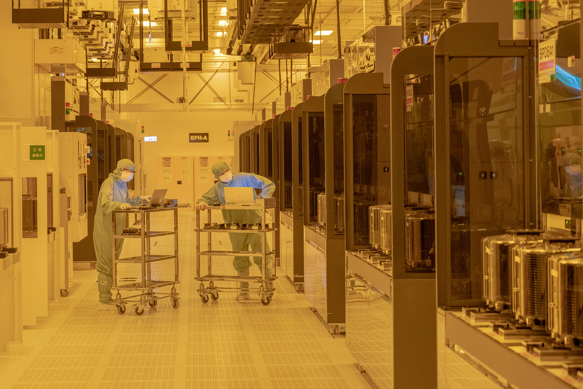"""TSMC workers in the """"clean room"""" where fabrication of chips takes place in the company's Hsinchu headquarters"""