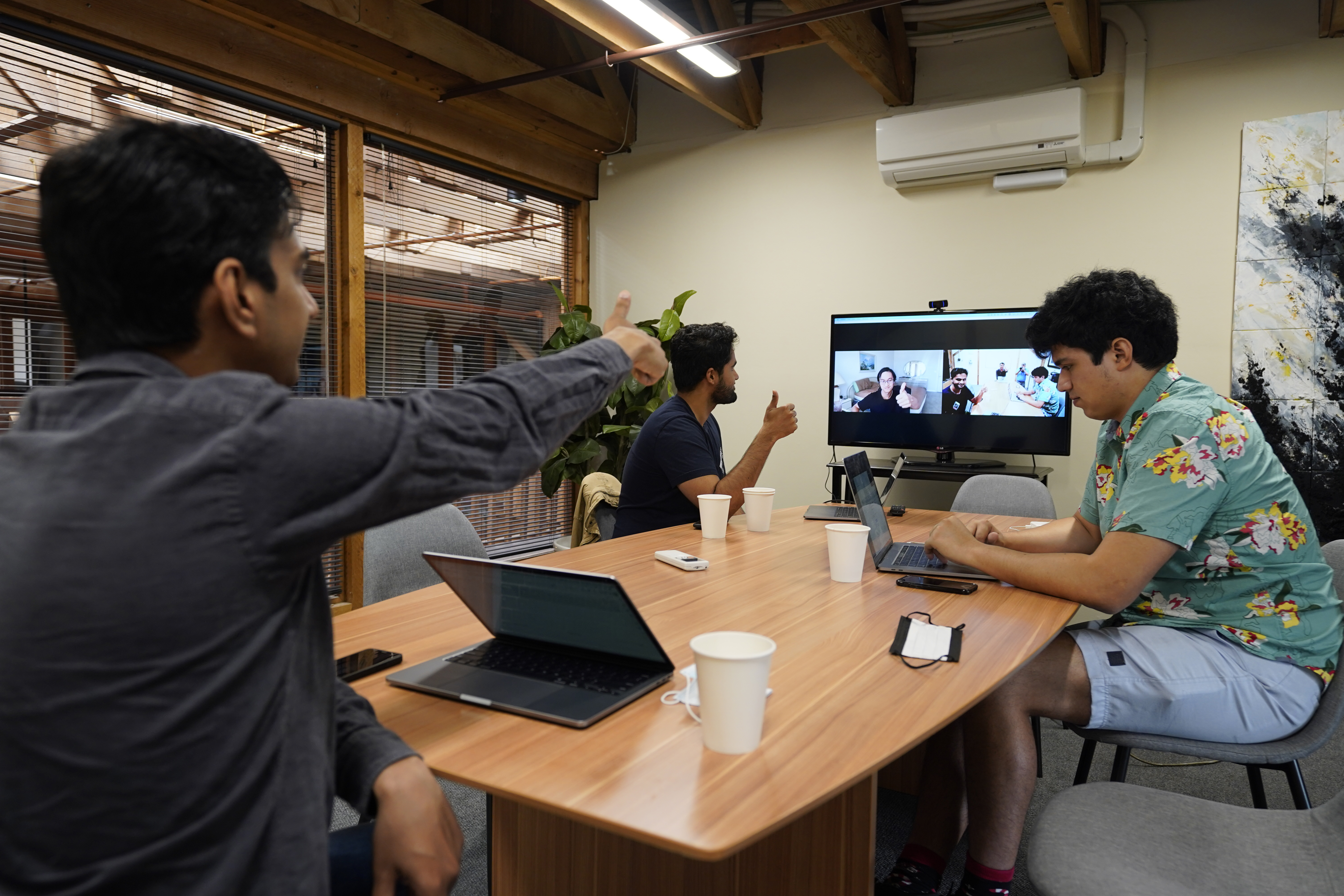 RunX CEO Ankur Dahiya, center, takes part in a meeting with employees JD Palomino, right, and Nitin Aggarwal, left, at a rented office in San Francisco, Friday, Aug. 27, 2021.