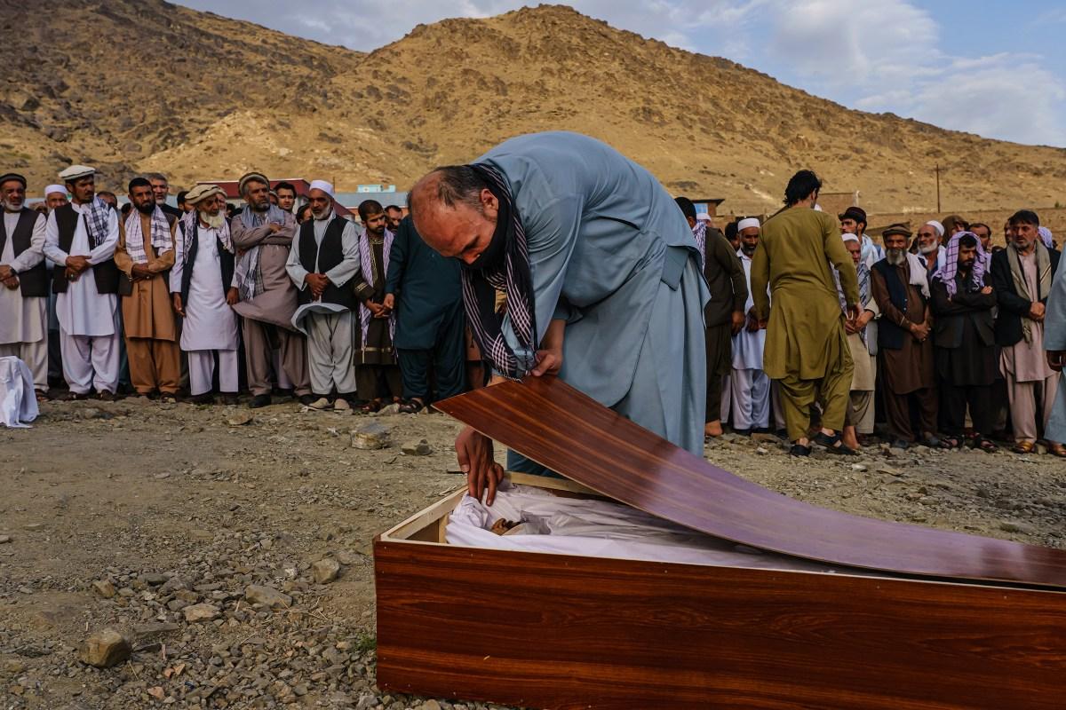 A man bids farewell to Zamarai Ahmadi in his casket during a mass funeral in Kabul on Aug. 30, 2021.