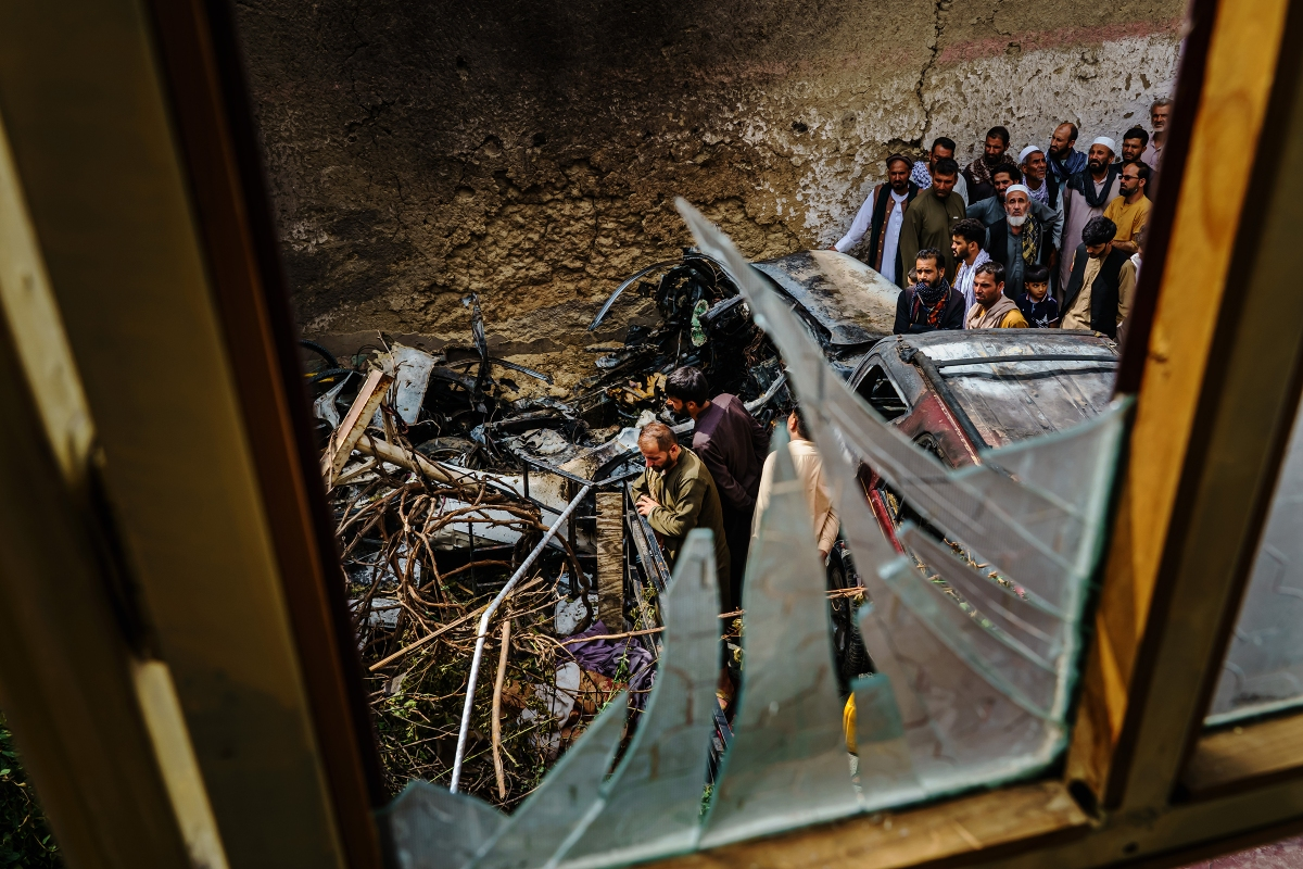 Relatives and neighbors of the Ahmadi family gathered around the incinerated husk of a vehicle, targeted a day earlier by an American drone strike, in Kabul on Aug. 30, 2021. Ten civilians, including seven children, were killed.