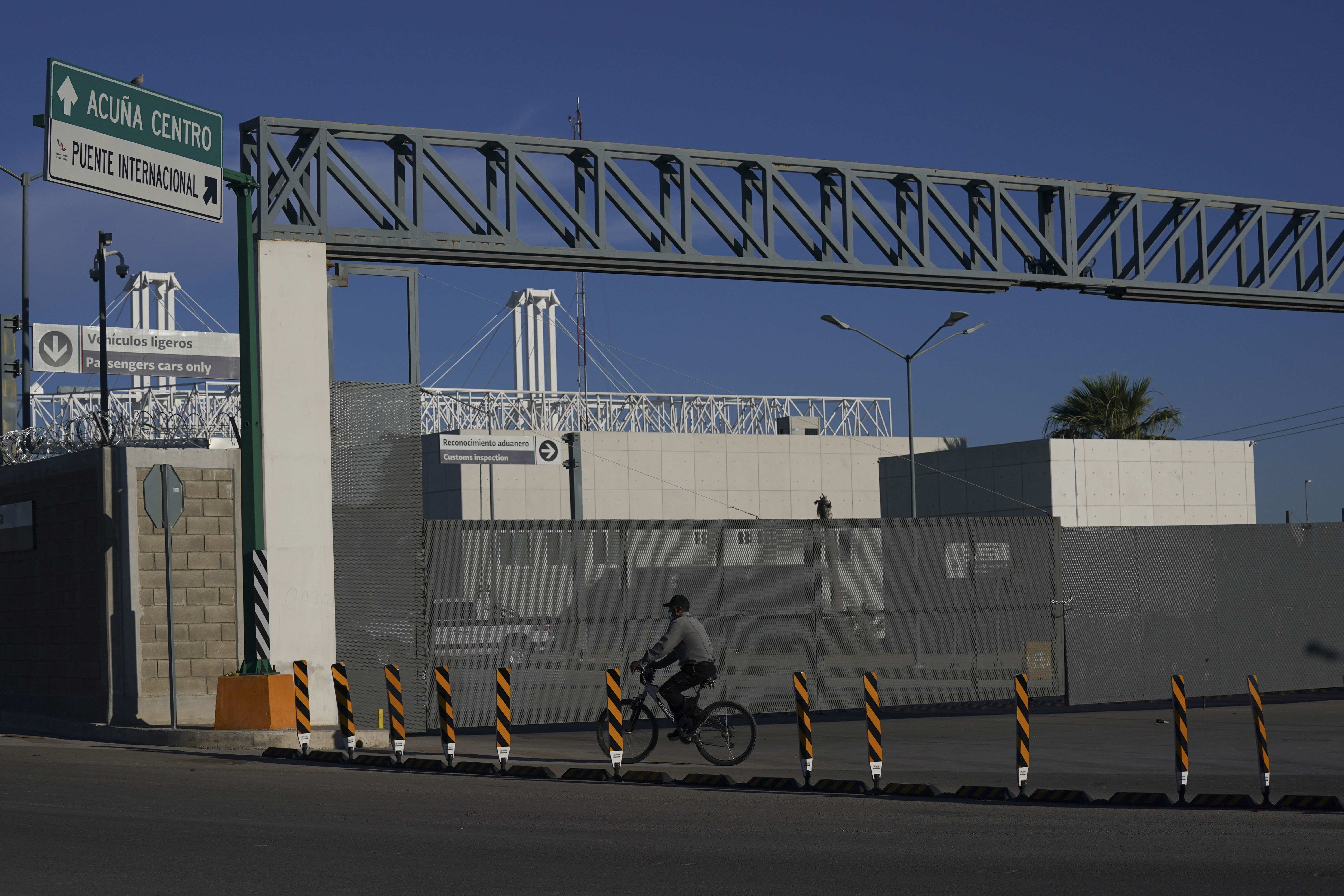 A man rides his bike past the closed main entrance of the international border bridge that connects the cities of Del Rio, Texas and Ciudad Acuna, Mexico, Friday, Sept. 24, 2021.