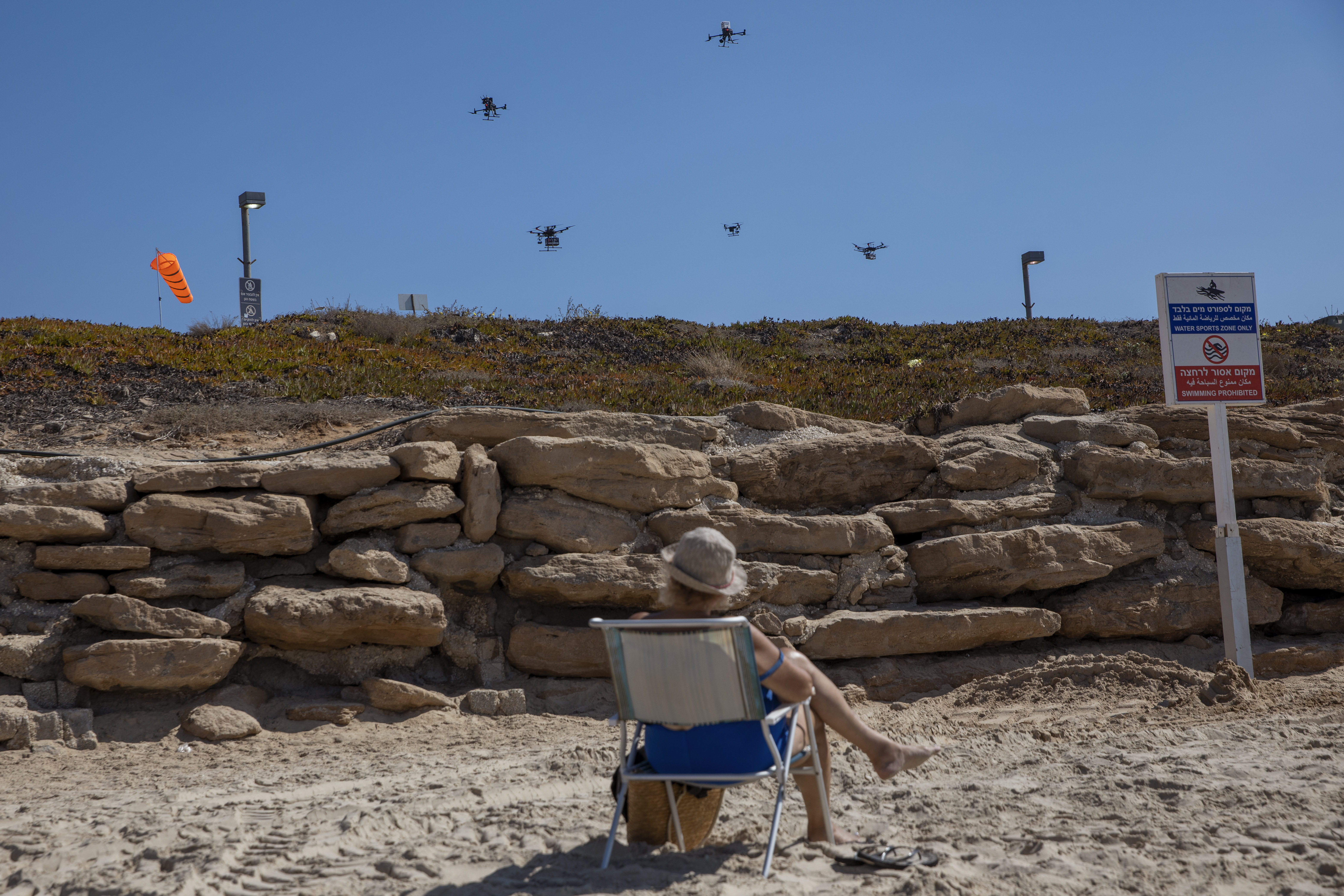 A woman looks at drones carrying goods as part of the National Drone Initiative demonstration for journalists over Tel Aviv, Israel, Monday, Oct. 11, 2021.