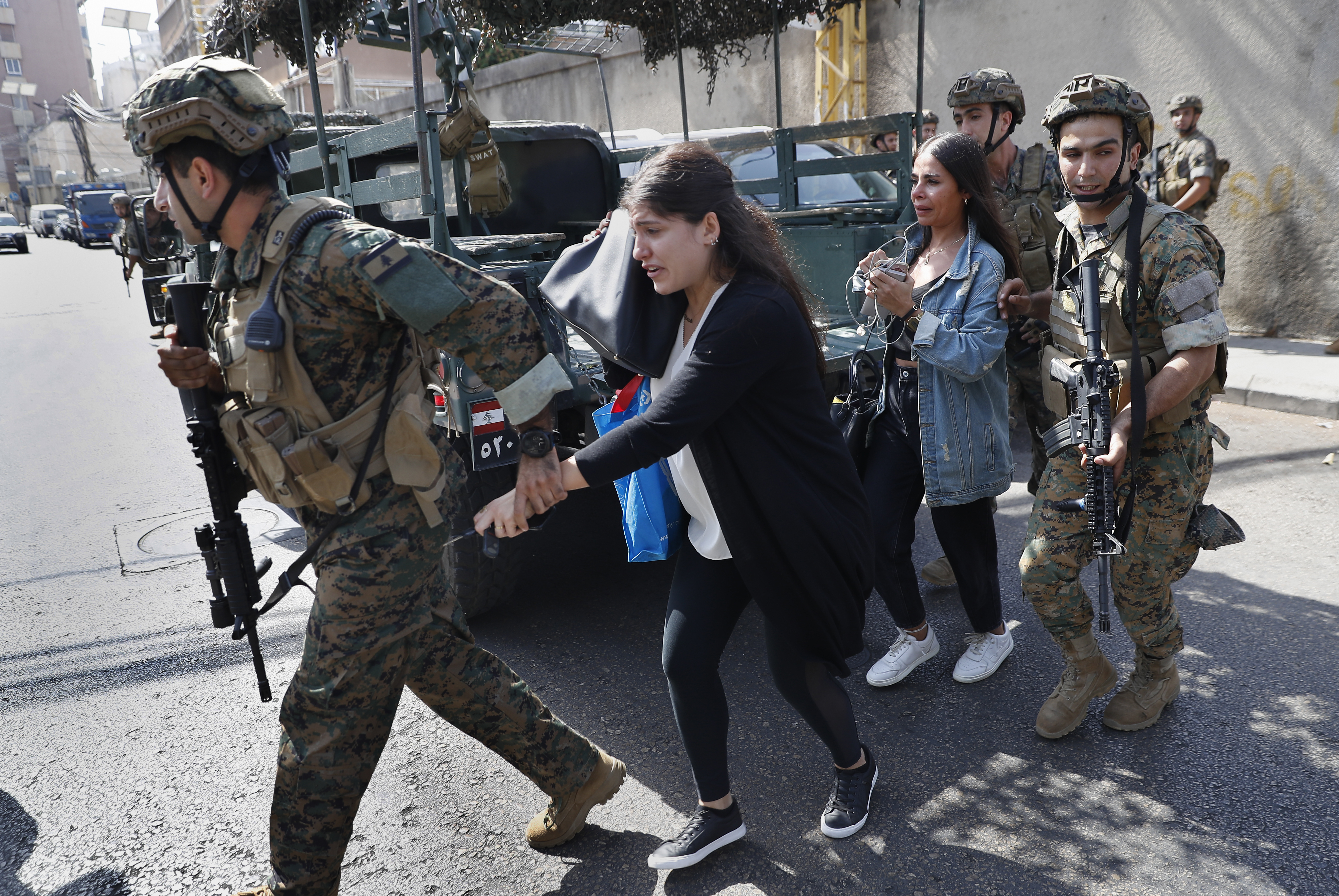 Lebanese army special forces soldiers assist teachers as they flee their school after deadly clashes erupted nearby along a former 1975-90 civil war front-line between Muslim Shiite and Christian areas at Ain el-Remaneh neighborhood, in Beirut, Lebanon, Thursday, Oct. 14, 2021.