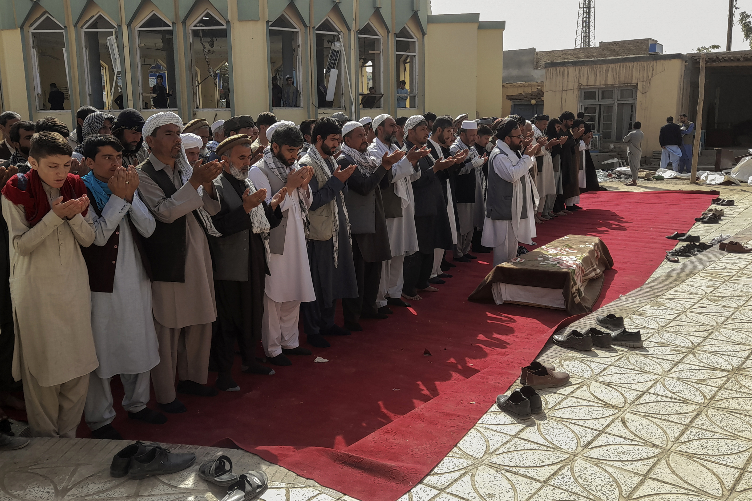 Relatives and residents pray during a funeral ceremony for victims of a suicide attack at the Gozar-e-Sayed Abad Mosque in Kunduz, northern Afghanistan, on, Oct. 9, 2021.