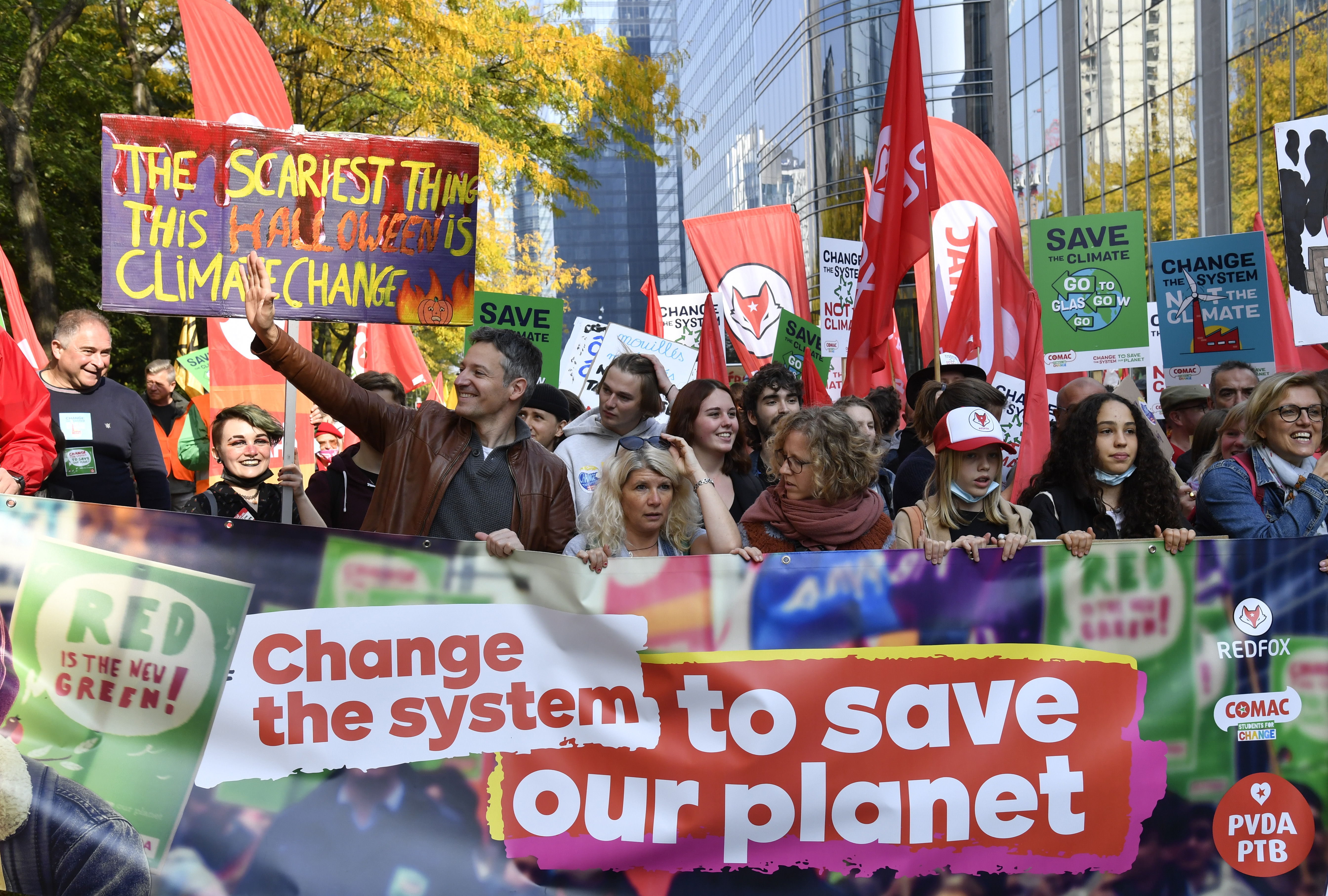 Protestors hold banners and signs as they participate in a climate march in Brussels, Belgium, on Oct. 10, 2021.