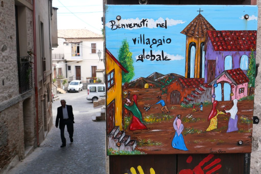 A welcoming sign reading  Welcome to the Global Village  is pictured in the small town of Riace, southern Italy, on June 4, 2019