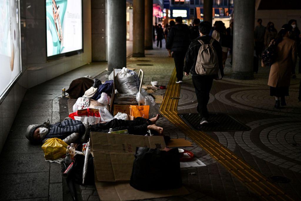 A homeless man sleeps on the pavement near Shinjuku station in Tokyo on November 18, 2020.