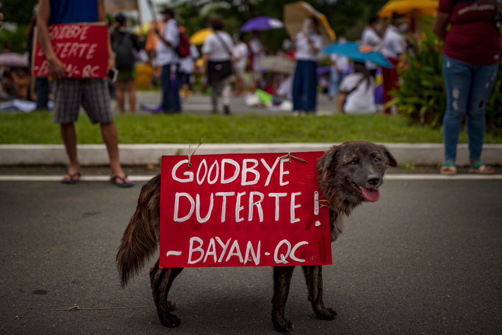 A dog is seen with placard as Filipino protesters attempt to march towards Philippine Congress to call for an end to Duterte's presidency on July 26, 2021 in Manila, Philippines.