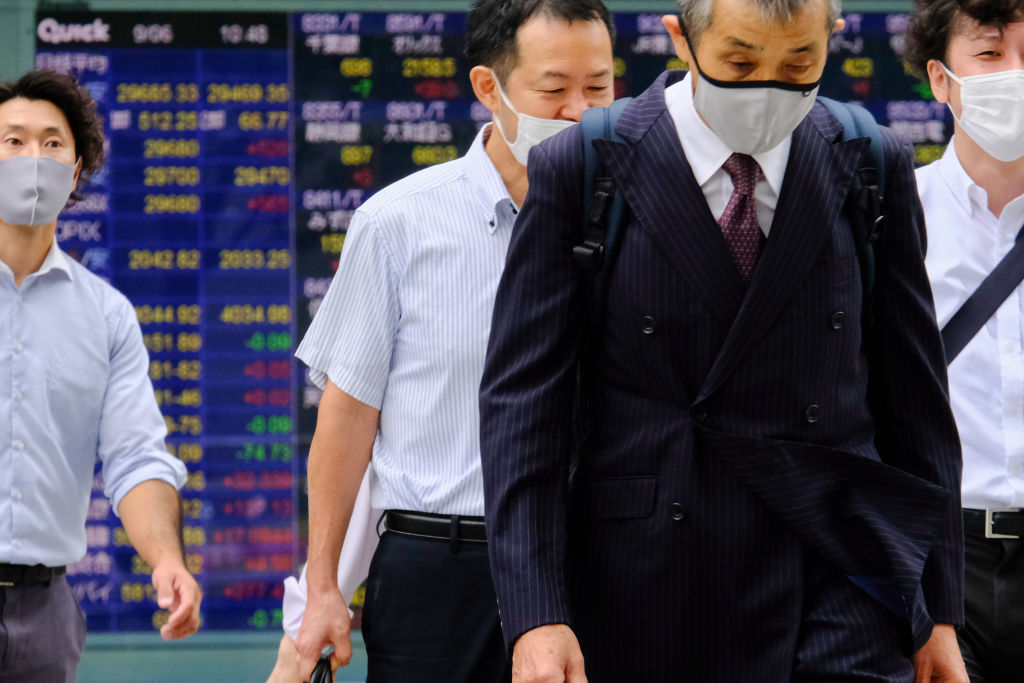 Japanese businessmen walk past a screen displaying the Nikkei share average and world stock indexes outside a Tokyo brokerage on Sept. 6, 2021