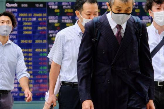 Japanese businessmen walk past a screen displaying Nikkei