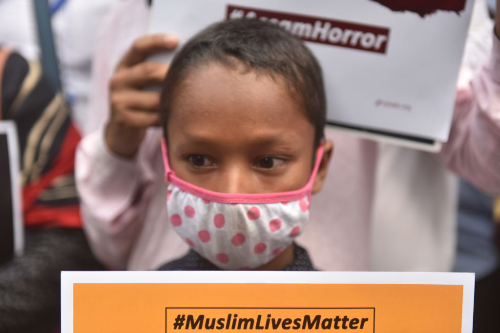 A boy holds a placard during a massive protest  in Kolkata, India on Sept. 25 against the killing of two Muslims in Assam.