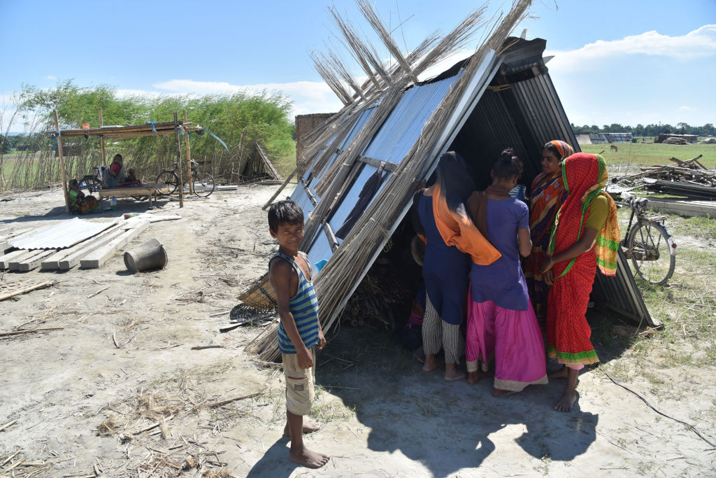 Villagers on Sept. 27 take shelter with their belongings after their house was demolished during an eviction drive, at Gorukhuti in the Darrang district of Assam, India