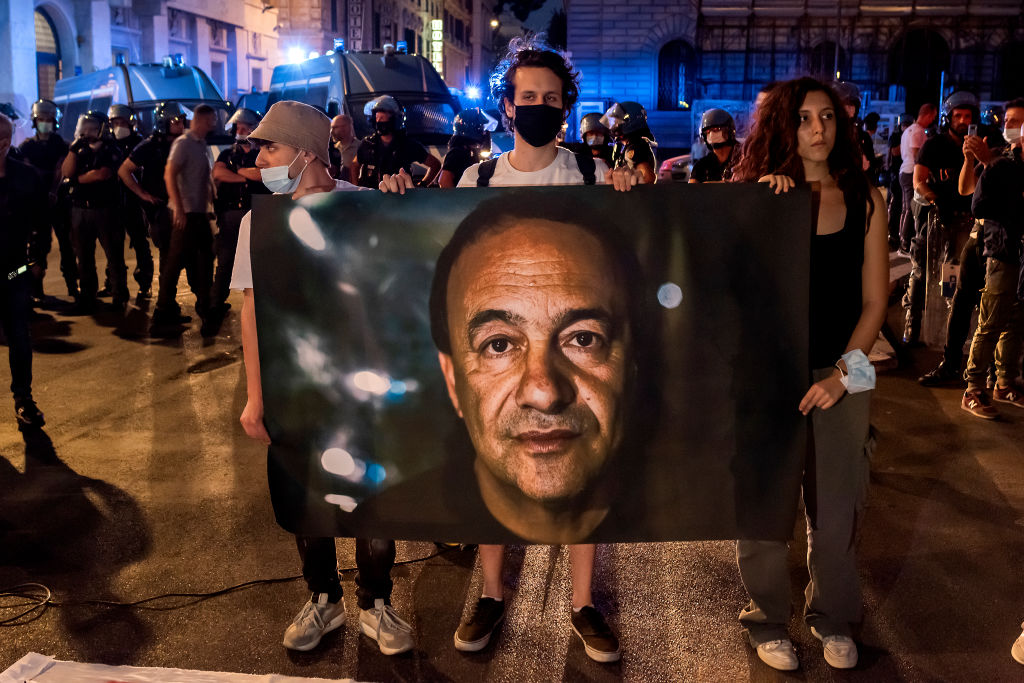 Anti-racism demonstrators hold a photo of Mimmo Lucano outside the High Council of the Judiciar as they protest against the condemnation of former Riace Mayor Mimmo Lucano, on Oct. 4, 2021 in Rome, Italy