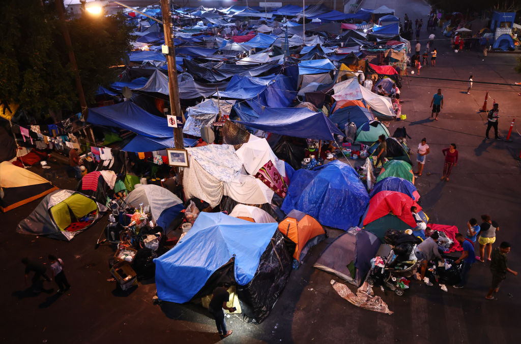 Asylum-seeking migrants gather at a makeshift camp on the Mexican side of the San Ysidro Port of Entry on July 20, 2021 in Tijuana, Mexico.