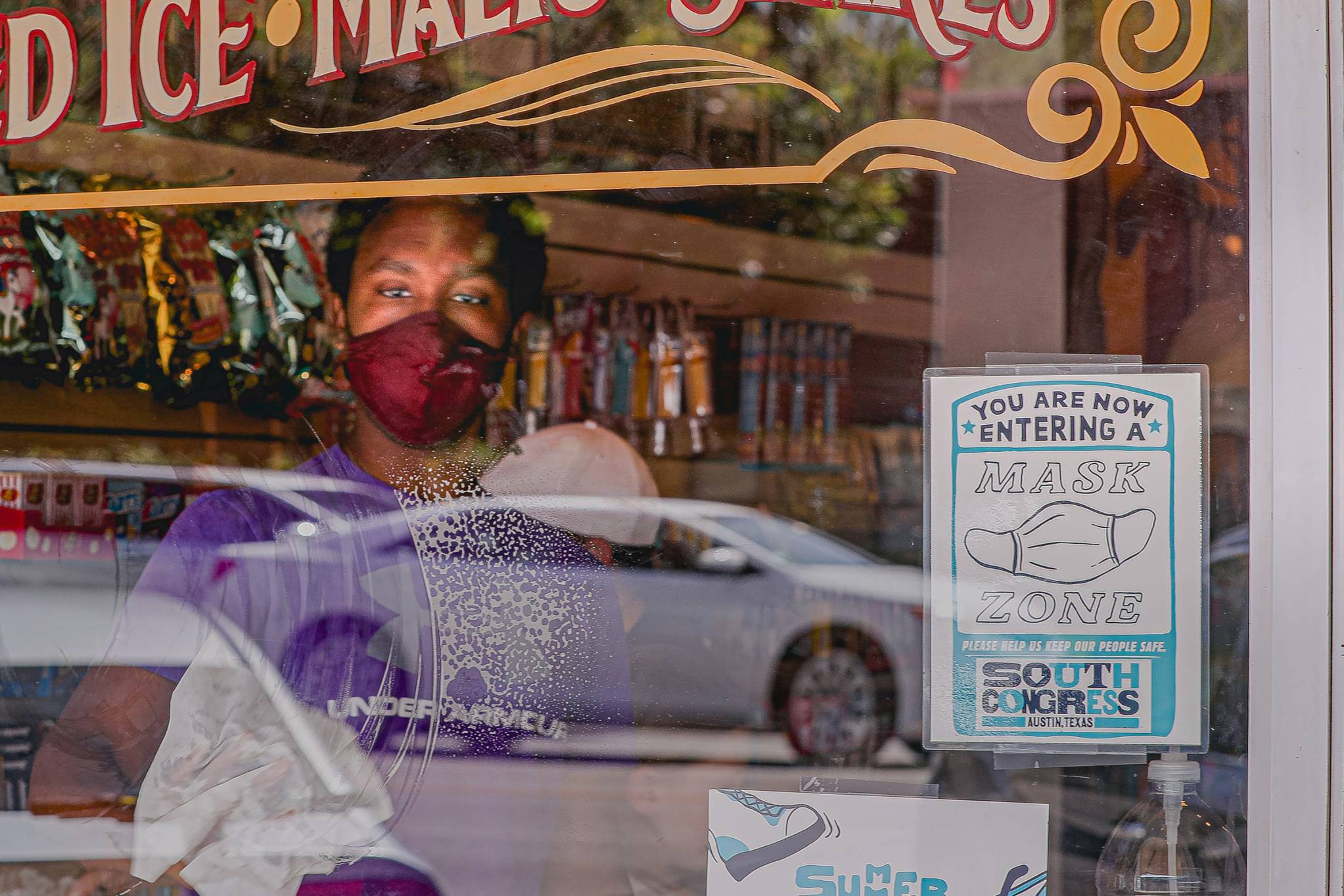 A store employee wearing a mask cleans a window with a sign requesting customers put on masks at a shop on Austin's South Congress Avenue on Sept. 30.
