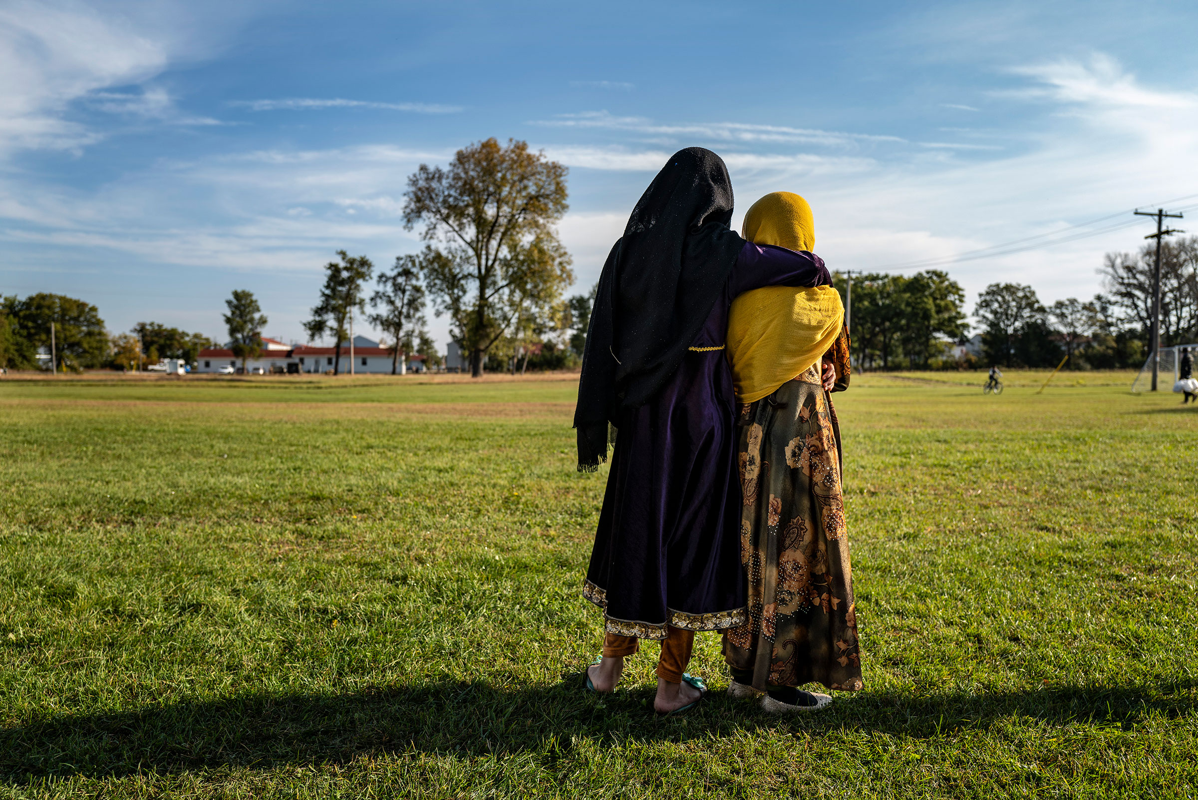 Afghan refugee girls watch a soccer match near where they are staying in the Village at the Ft. McCoy U.S. Army base on September 30, 2021 in Ft. McCoy, Wisconsin. There are approximately 12,600 Afghan refugees at the base under Operation Allies Welcome.