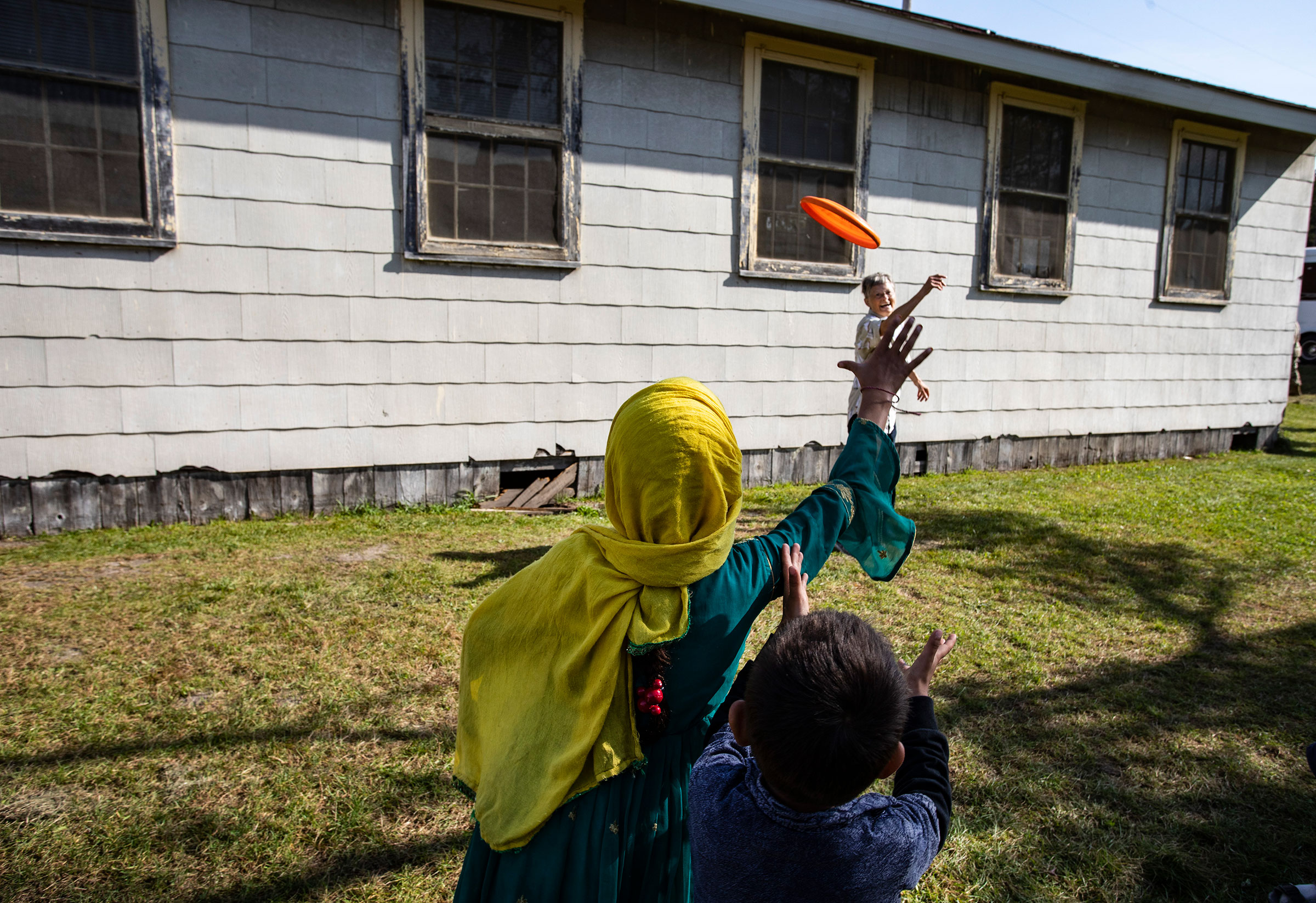 Volunteer Sandra Hoeser plays frisbee with Afghan refugees at the Ft. McCoy U.S. Army base on September 30, 2021 in Ft. McCoy, Wisconsin.