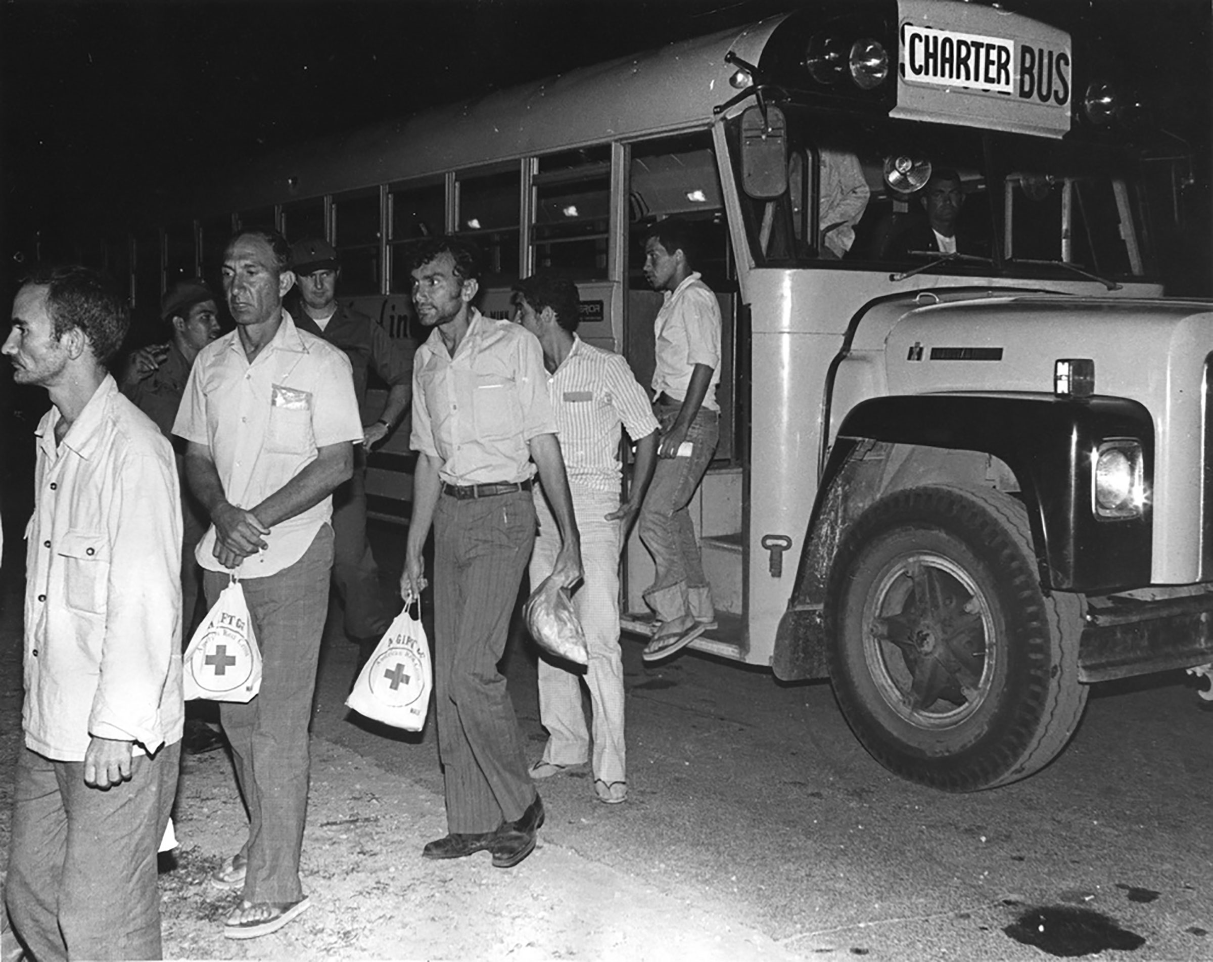 Cuban refugees step off a bus and into a holding area at Fort McCoy in 1980 after a ride from the La Crosse Municipal Airport. Fort McCoy served as a processing center for Cuban refugees from the Mariel Boatlift.