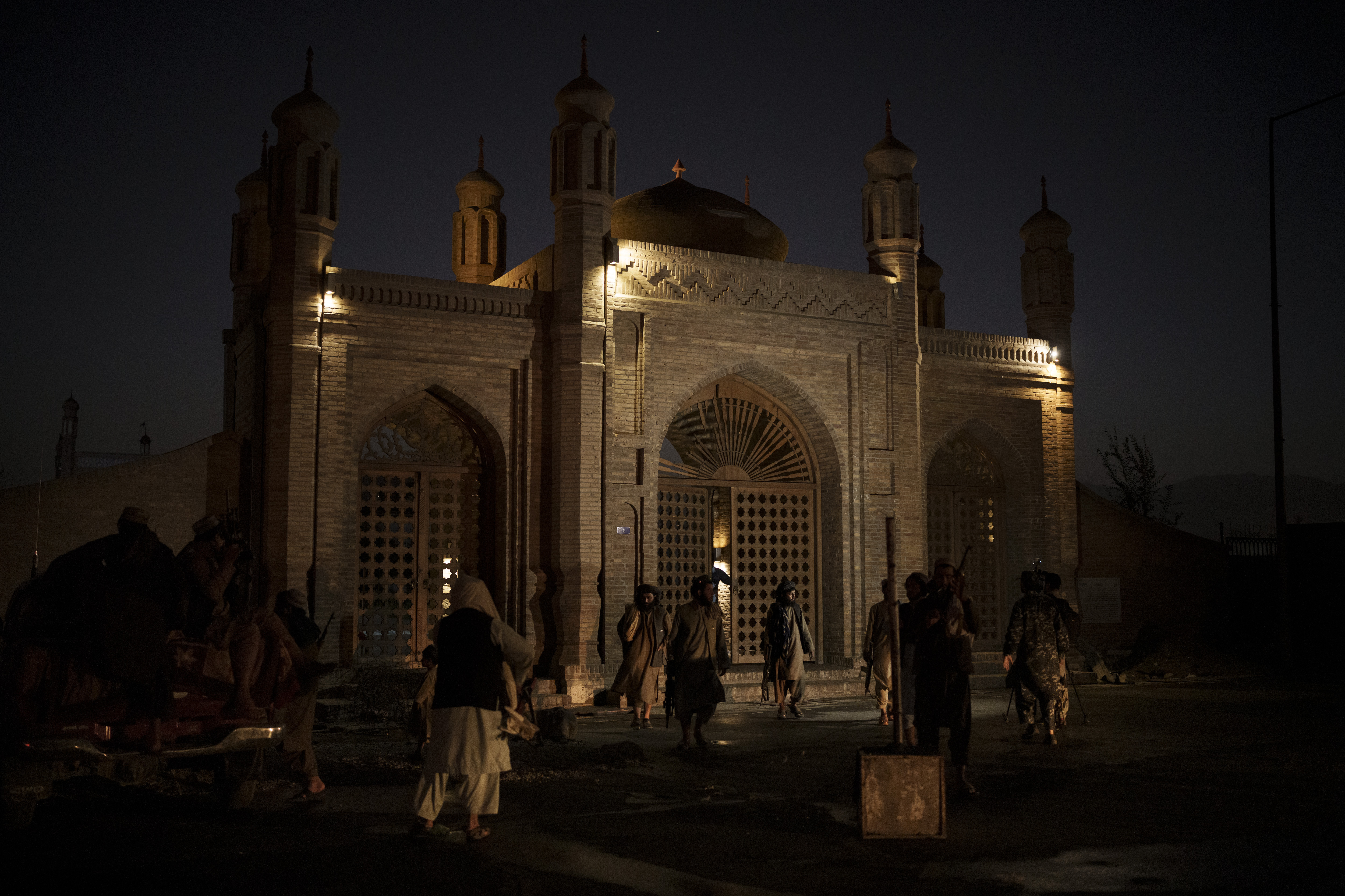 Taliban fighters walk at the entrance of the Eidgah Mosque after an explosion in Kabul, Afghanistan, on Oct. 3, 2021.