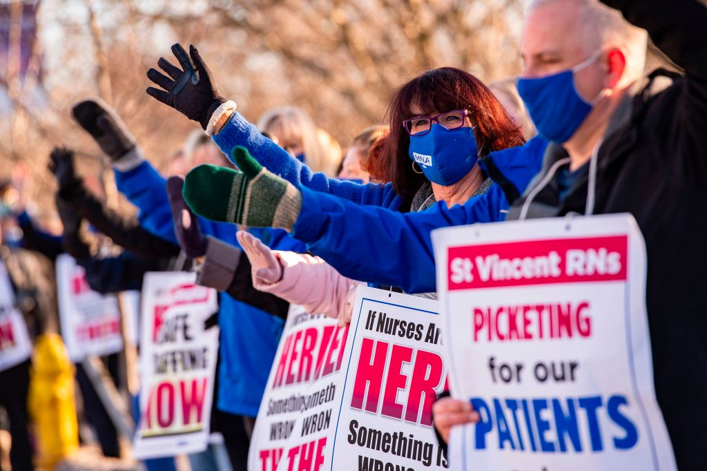 Registered Nurses and supporters stand in a picket line and wave to cars as they drive by outside St. Vincent Hospital in Worcester, Massachusetts on February 24, 2021.